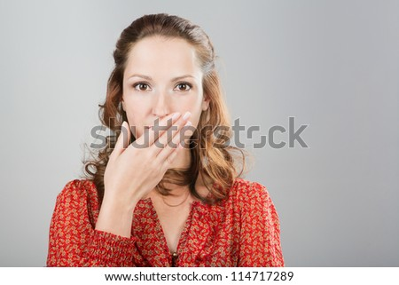 Secret woman saying be quiet. Girl with hand in front of mouth. shut up.In red blouse. Grey background. Studio shot. - stock photo