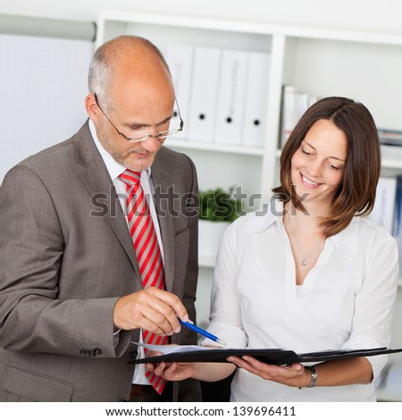 secretary and businessman looking at file in the office