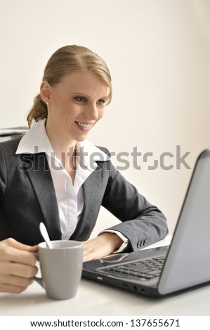 Secretary behind a laptop holding a coffeecup. Face is in focus.