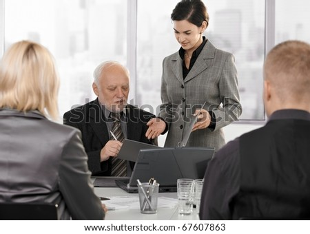 Secretary getting contract to sign by senior executive at businessmeeting.? - stock photo