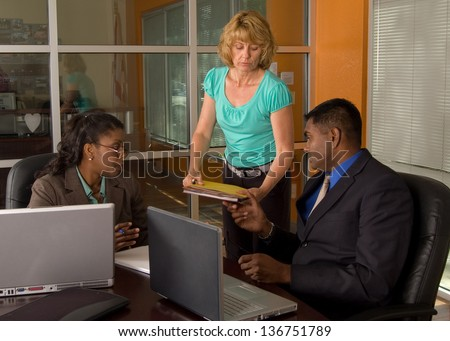 Secretary hands folders to a businessman who is sitting next to a businesswoman with laptop computers - stock photo
