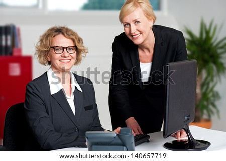 Secretary helping her boss during work hours - stock photo