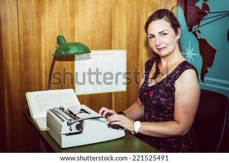 Secretary in a sixties style office, with old typewriter. - stock photo