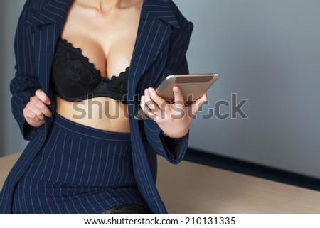 Secretary in black bra online flirt on tablet, desire - stock photo