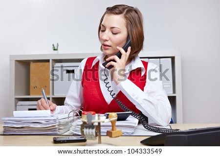 Secretary in business office taking notes while talking on the phone - stock photo