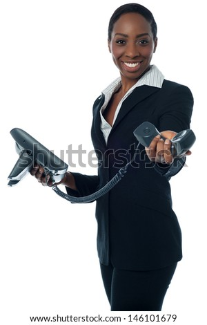 Secretary passing phone receiver to her boss - stock photo