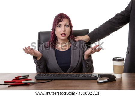 secretary sitting at desk with a mans hand on her shoulder  feeling uncomfortable - stock photo