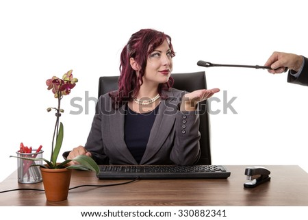 secretary sitting at desk with hand out awaiting to be slapped by a man holding a riding whip - stock photo