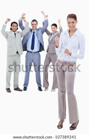 Secretary smiling and clenching her fists with very enthusiastic business people behind her against white background - stock photo