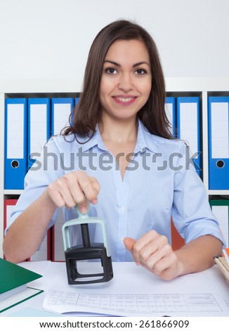 Secretary with long dark hair and stamp at office  - stock photo