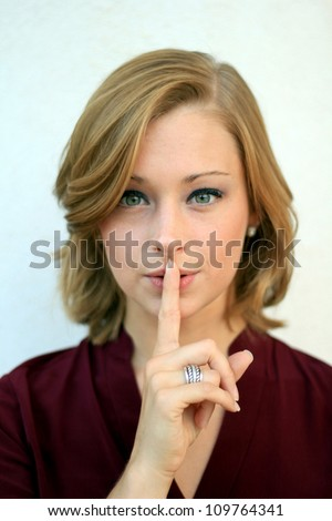 Secretive, Attractive Professional Business Woman Motioning to be Quiet - stock photo