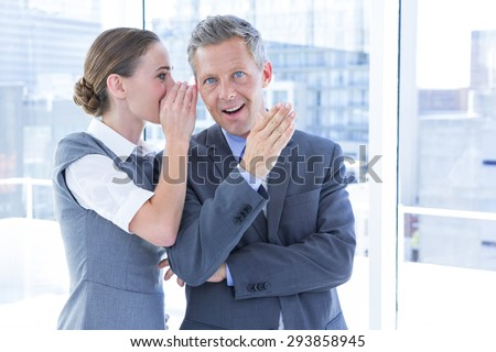 Secretive business colleagues whispering in the office - stock photo