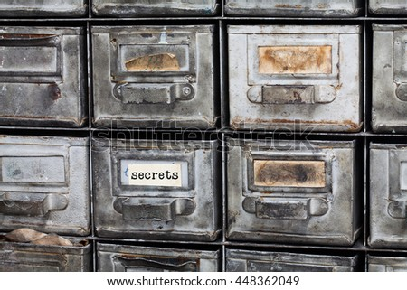 Secrets concept image. Closed archive storage, filing cabinet interior. aged silver metallic boxes with index cards. library service information security management. - stock photo