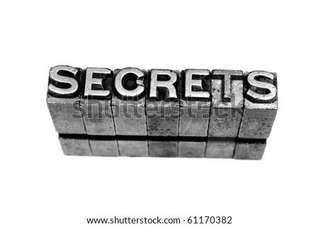 SECRETS written in metallic letters on a white background - stock photo