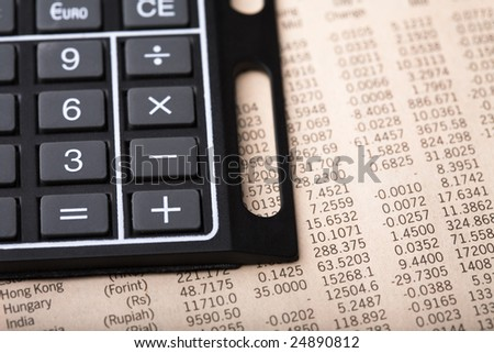 Section of a calculator placed on currency exchange rates page of a financial newspaper - stock photo