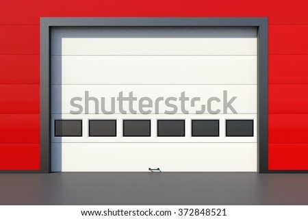 Sectional industrial door with windows on red industrial wall - stock photo