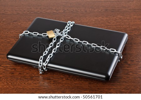secured laptop on wooden background - stock photo