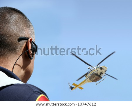 Security agent coordinating surveillance with helicopter - stock photo