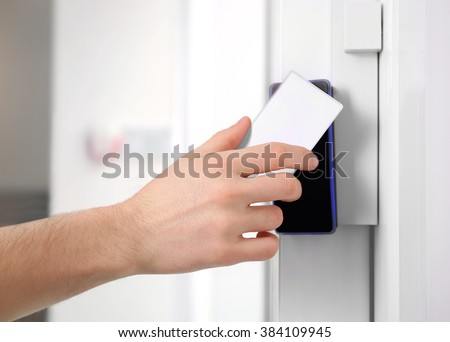 Security alarm keypad with male hand and card, closeup - stock photo