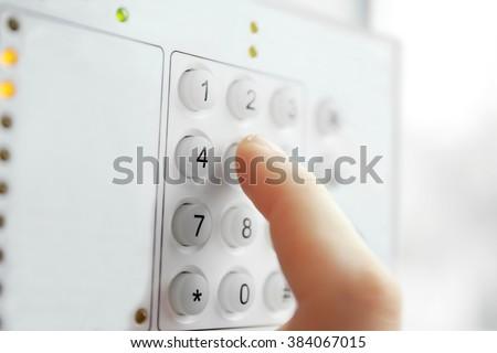 Security alarm keypad with male hand, closeup - stock photo