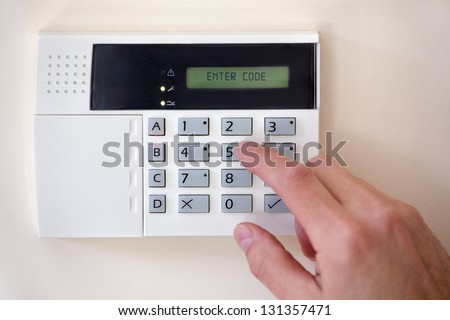 Security alarm keypad with person arming the system - stock photo