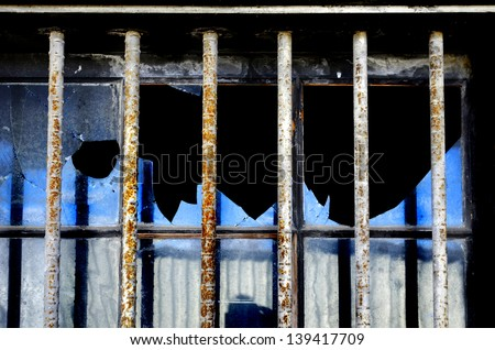 Security bars on broken window to prevent breaking into building - stock photo