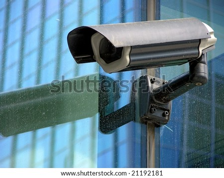 security black camera on glass facade - stock photo