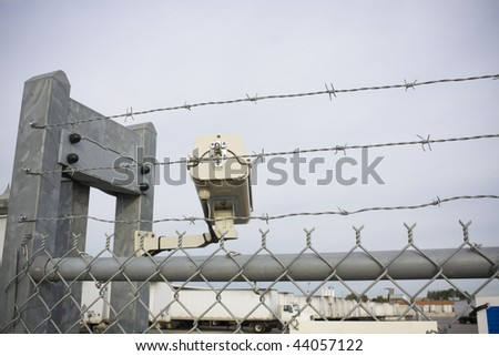Security cam overlooking truck yard with chain-link fence and barbed wire - stock photo