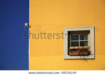 Security camera and yellow wall - stock photo
