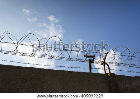 Security camera behind barbed wire fence stretched around prison walls - stock photo