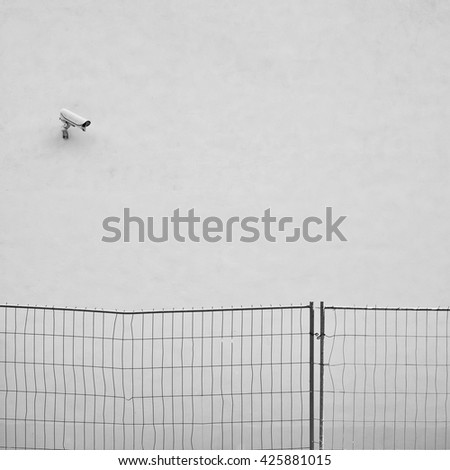 Security camera CCTV on the crumpled stucco wall - stock photo