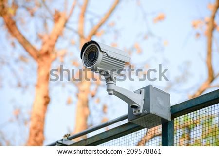 Security Camera CCTV  over fence blue sky - stock photo