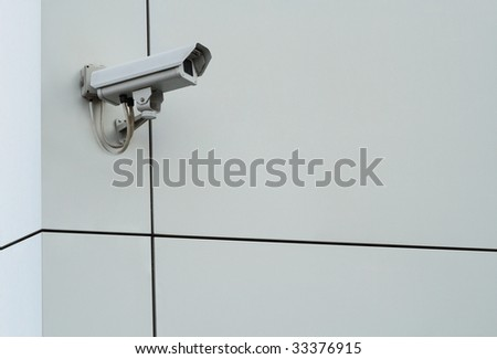 Security camera. Digital camcorder on gray plastic facade wall - stock photo