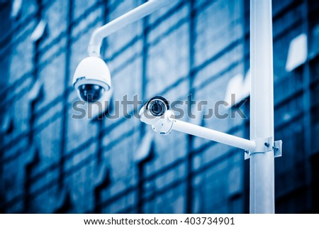 security camera in front of the office building,blue toned image. - stock photo