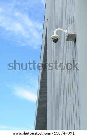 Security camera is install corner outside of building with blue sky backdrop - stock photo