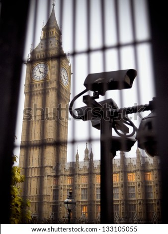 Security camera is monitoring the area behind the bars of the metal fence around Big Ben and The Houses Of Parliament - stock photo