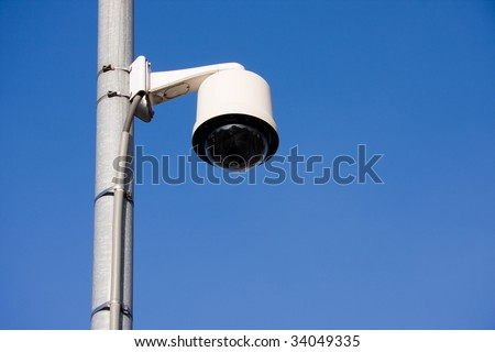 Security camera located on a post over a street