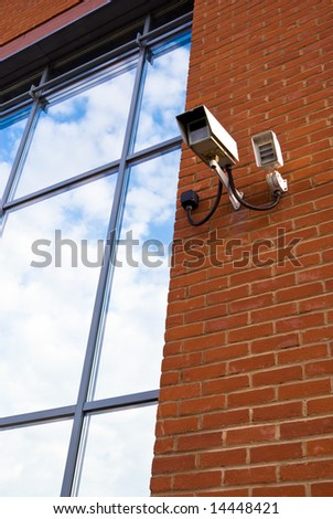 Security camera looking out from a window reflecting sky - stock photo