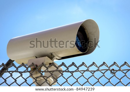 Security Camera on a Chain link Fence at the Open Sky - stock photo