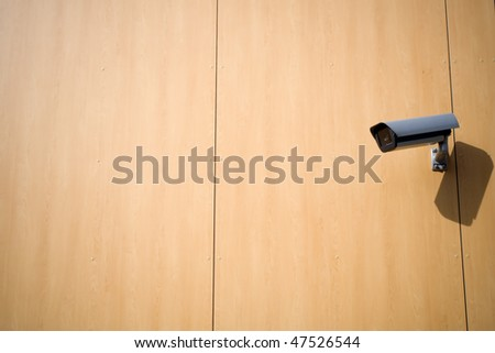 Security camera on a wall outside building - stock photo