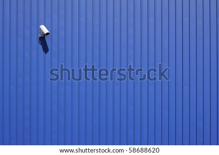 security camera on blue metallic wall with copy space
