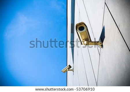 Security camera on building and blue sky - stock photo