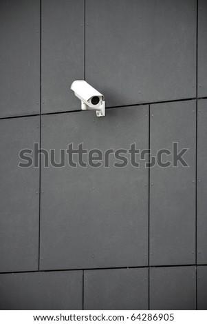 Security camera on dark modern building - stock photo