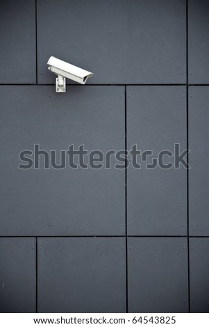 Security camera on dark modern building - stock photo