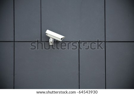 Security camera on dark modern building, technology concept