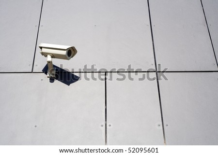 Security camera on gray abstract wall background