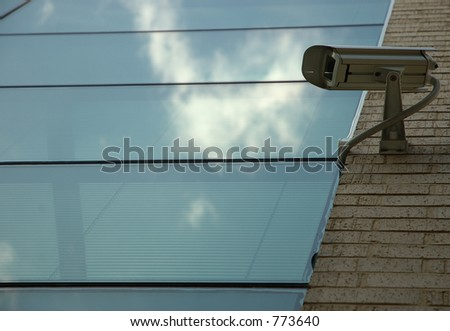 Security camera on office wall with glass window and cloud reflection