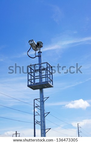 Security camera on podium against blue sky - stock photo