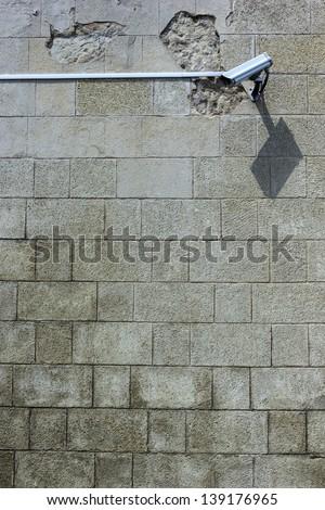 Security camera on stone wall. - stock photo