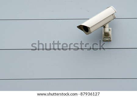 Security camera on the aluminum wall - stock photo